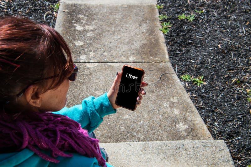 Kobiety obsiadanie na zewnątrz patrzeć przyglądający jej telefonu komórkowego ekran który mówi Uber obrazy royalty free