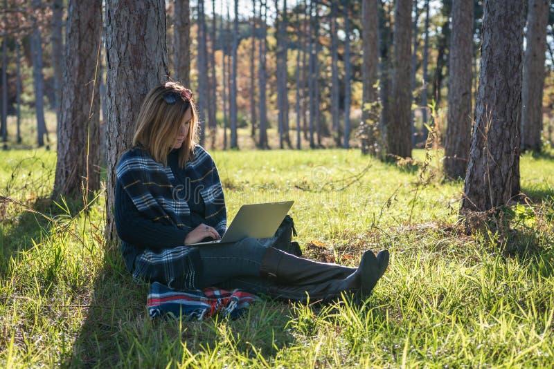 Kobiety obsiadanie przeciw drzewu z laptopem fotografia stock