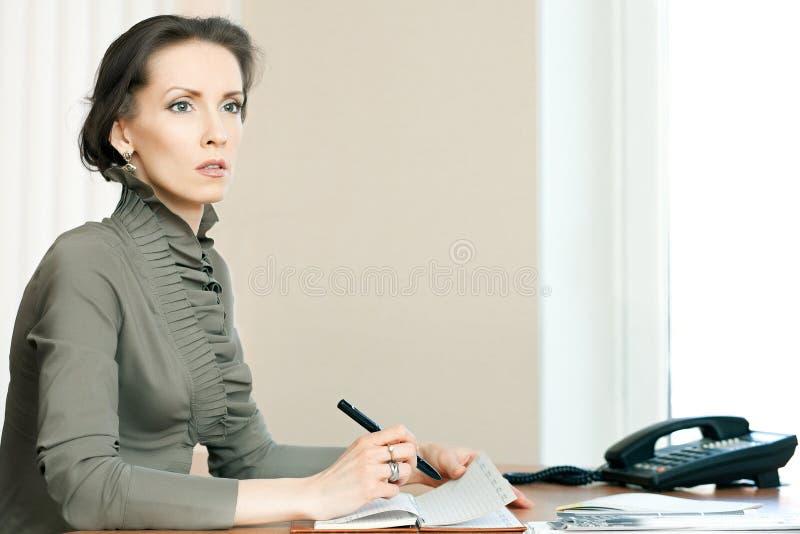 Kobiety obsiadanie przy biurkiem bierze notatki w dzienniczku obraz stock