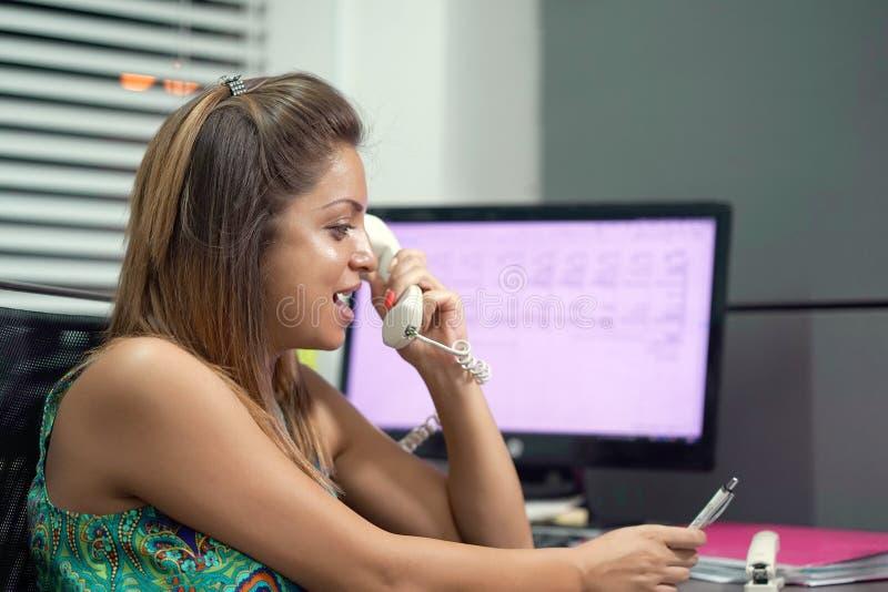 Kobiety obsiadanie przy jej biurka działaniem, odpowiadaniem i rozmowa telefonicza zdjęcia stock