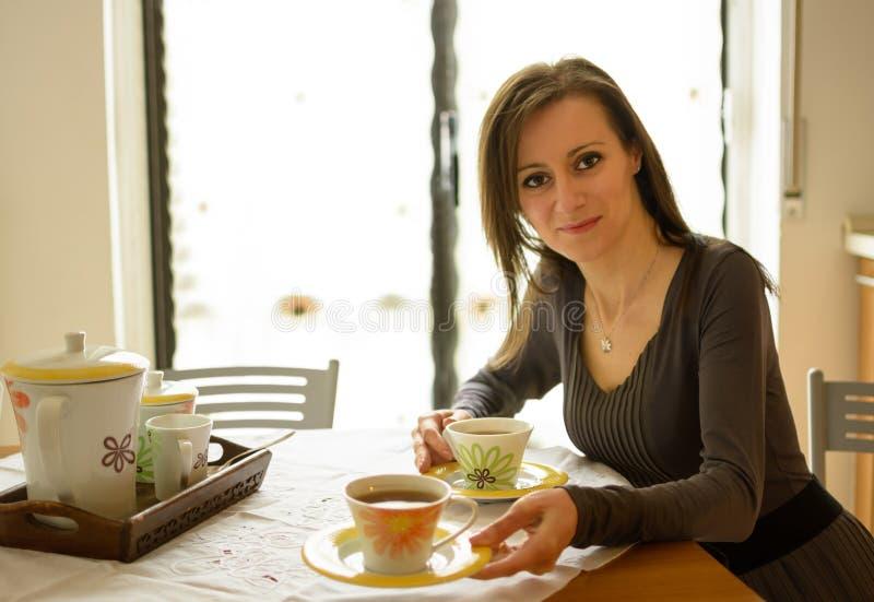Kobiety obsiadanie przy stołem oferuje filiżankę herbata obraz stock