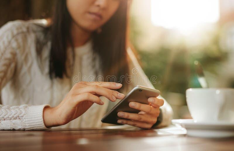 Kobiety obsiadanie przy stołowym używa telefonem komórkowym fotografia stock