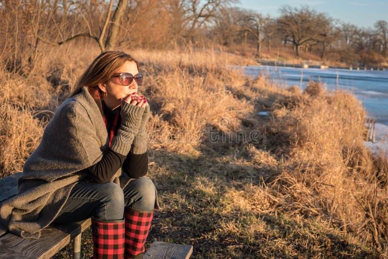 Kobiety obsiadanie wzdłuż zamarzniętego jeziora ogląda zmierzch w zimie zdjęcia royalty free