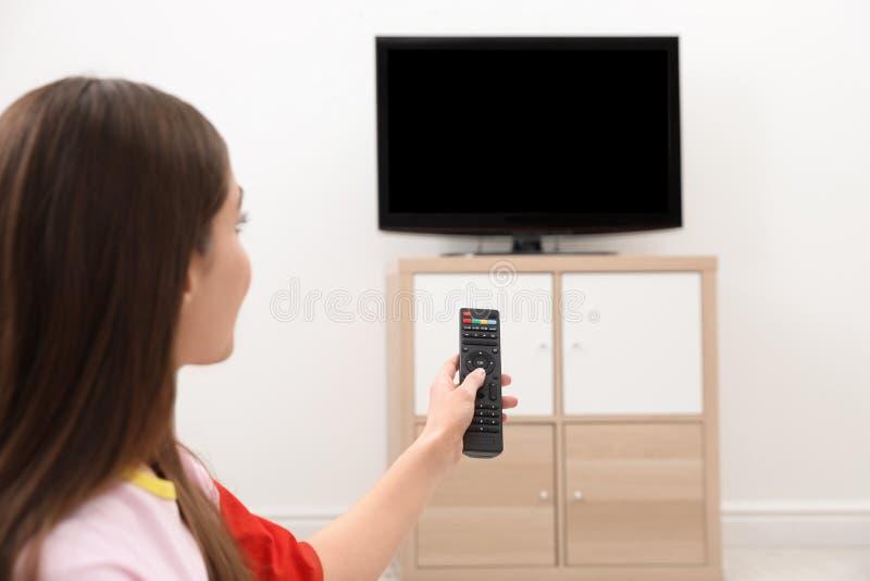 Kobiety odmieniania kanał telewizyjny z pilotem do tv w żywym pokoju obrazy stock