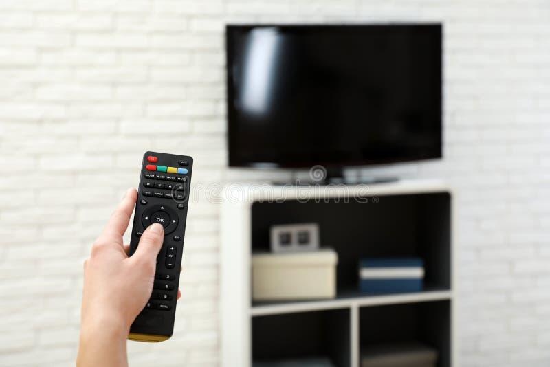 Kobiety odmieniania kanał telewizyjny z pilotem do tv w żywym pokoju, ostrość na ręce obraz royalty free