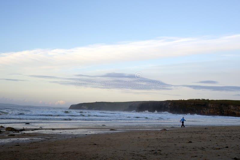 Kobiety odprowadzenie przy skalistą zimno plażą obrazy stock