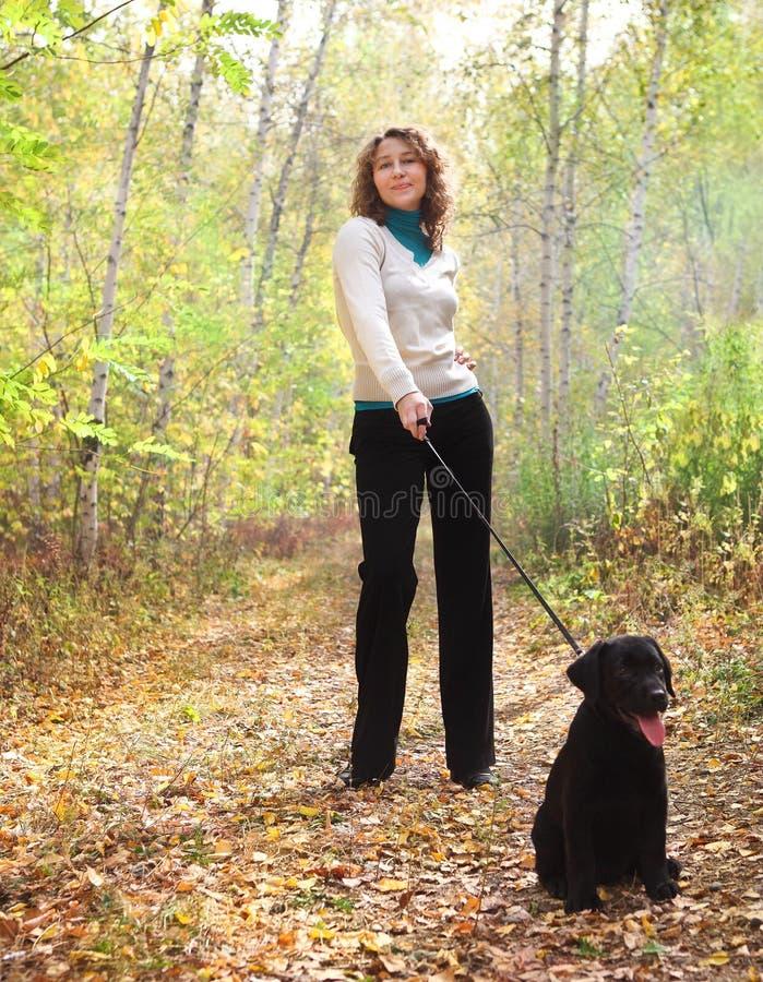 Kobiety odprowadzenie z czarny labradora aporteru szczeniakiem obrazy stock