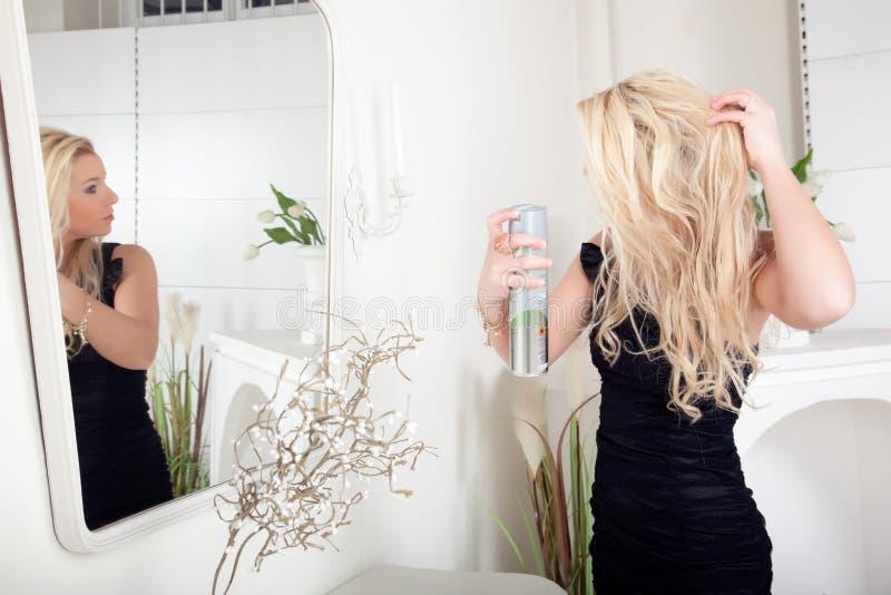 Kobiety opryskiwania lakier do włosów na jej włosy obrazy royalty free