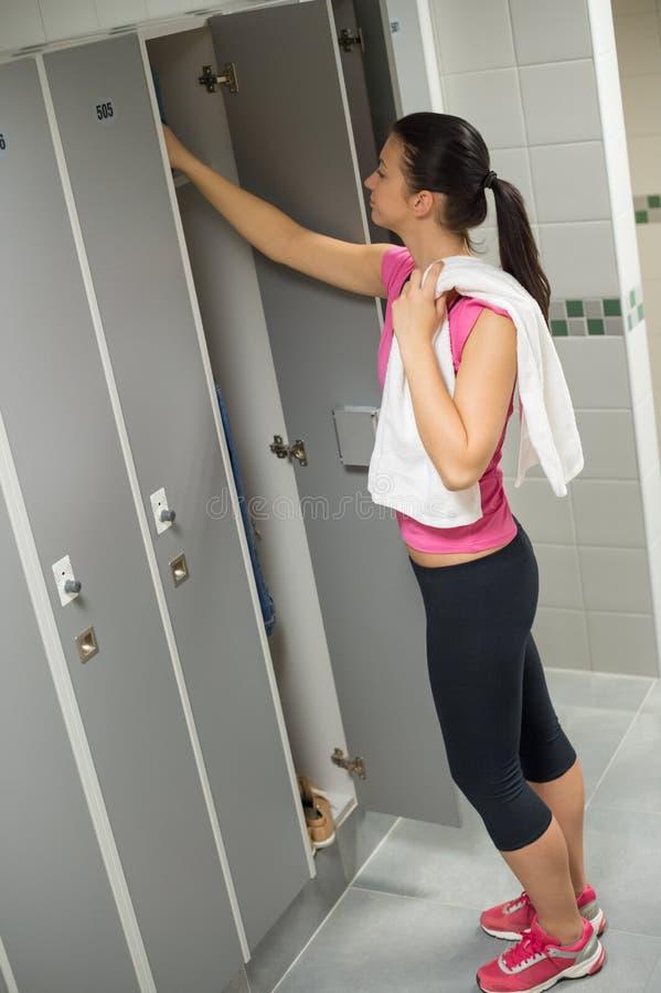 Kobiety otwarcia szafka przy gym fotografia stock