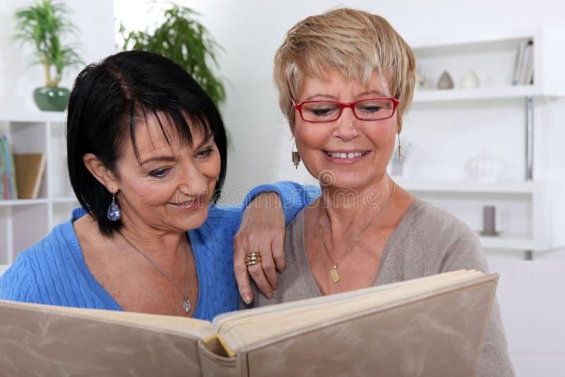 Kobiety patrzeje album fotograficzny zdjęcia stock