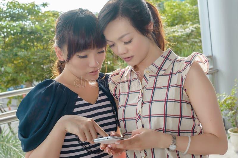 Kobiety patrzeje coś na telefonie komórkowym fotografia royalty free