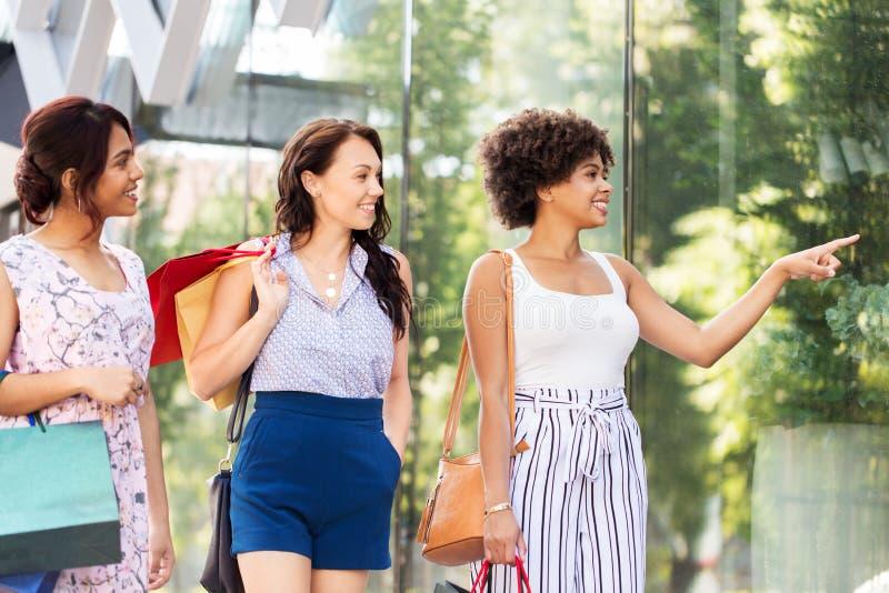 Kobiety patrzeje sklepowego okno z torba na zakupy fotografia stock