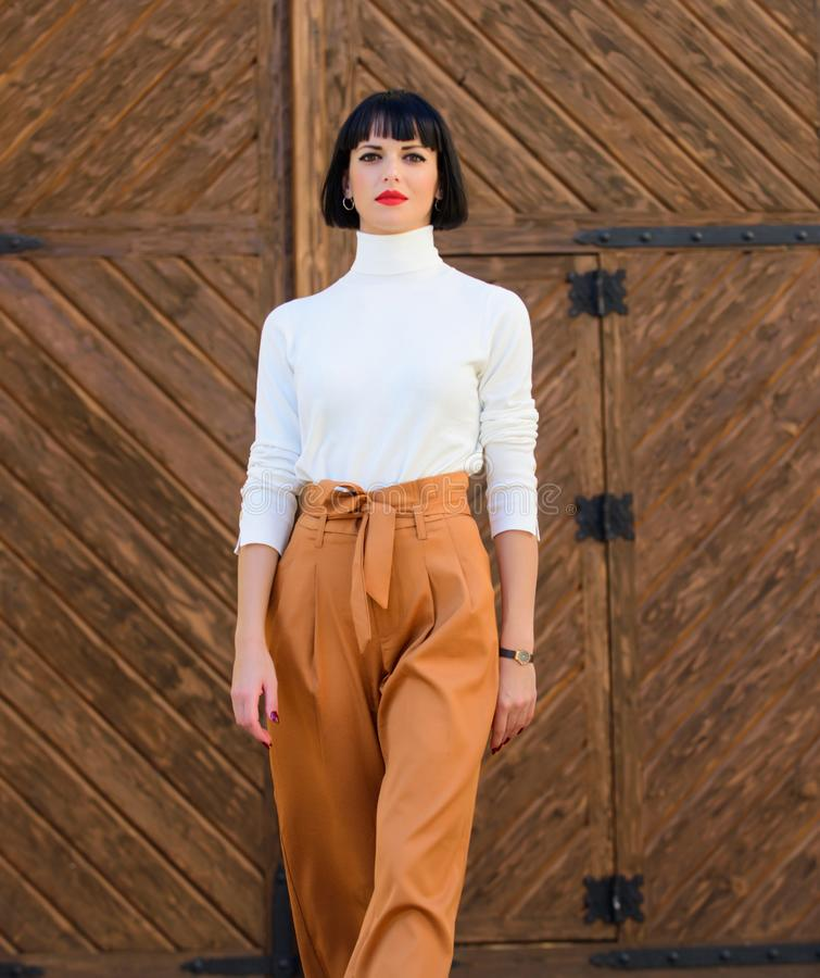 Kobiety pewnie spacer Kobiety brunetki stojaka outdoors modny drewniany tło mody i stylu pojęcie dziewczyna zdjęcia stock