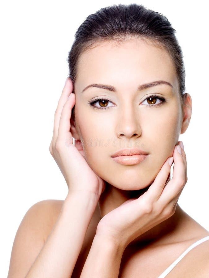 Kobiety piękny uderzanie jej czysty twarz fotografia stock