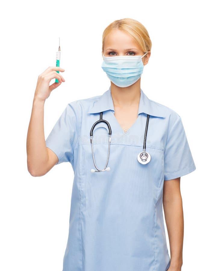 Kobiety pielęgniarka w maskowej mienie strzykawce lub lekarka zdjęcie stock