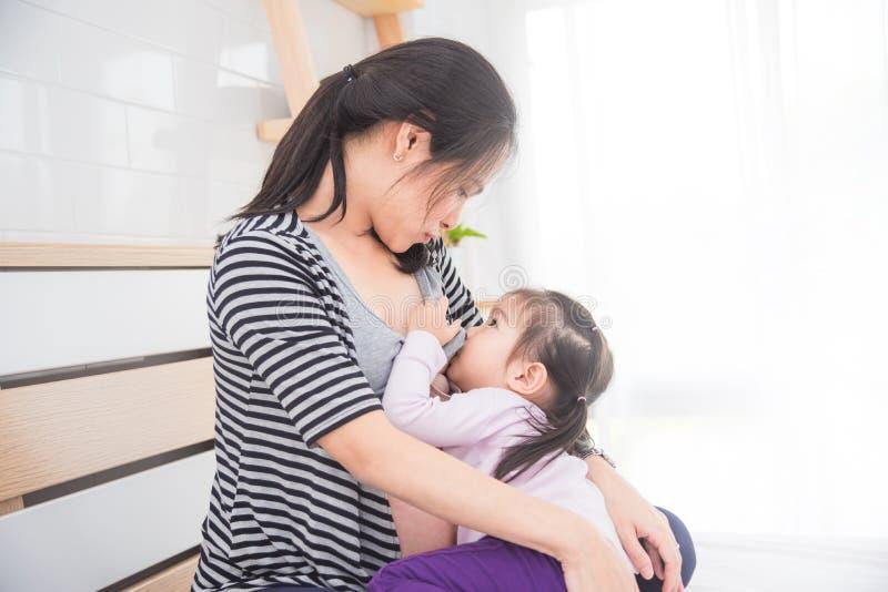 Kobiety pierś - karmiący jej córki w domu zdjęcia royalty free