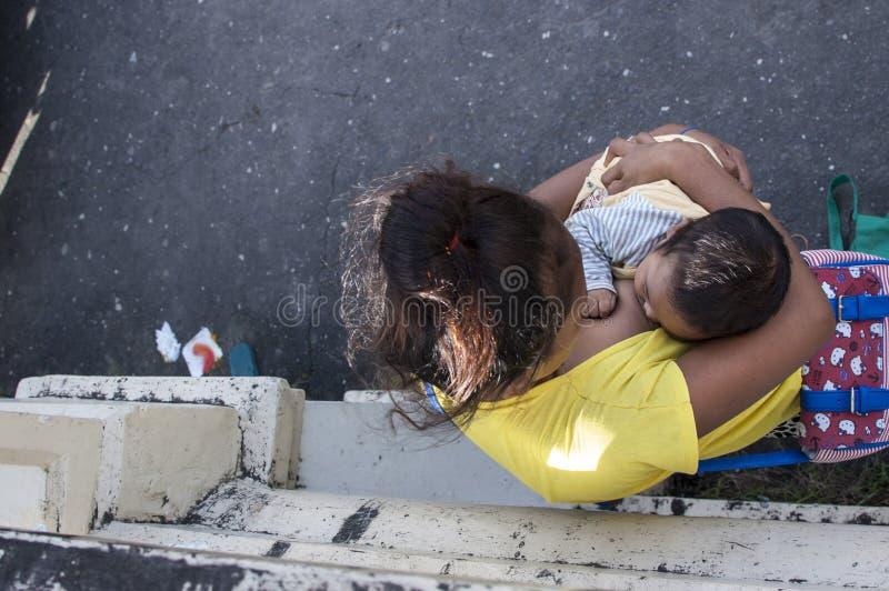 Kobiety pierś - karmić dziecka sprzedaje świeczki przy kościelnym jardem zdjęcia royalty free