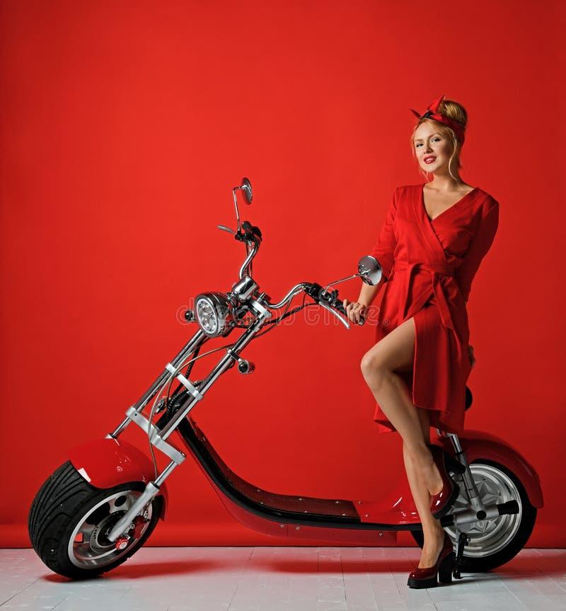 Kobiety pinup stylu przejażdżki elektrycznego samochodu nowego motocyklu rowerowa hulajnoga teraźniejsza dla nowego roku 2019 zdjęcia stock
