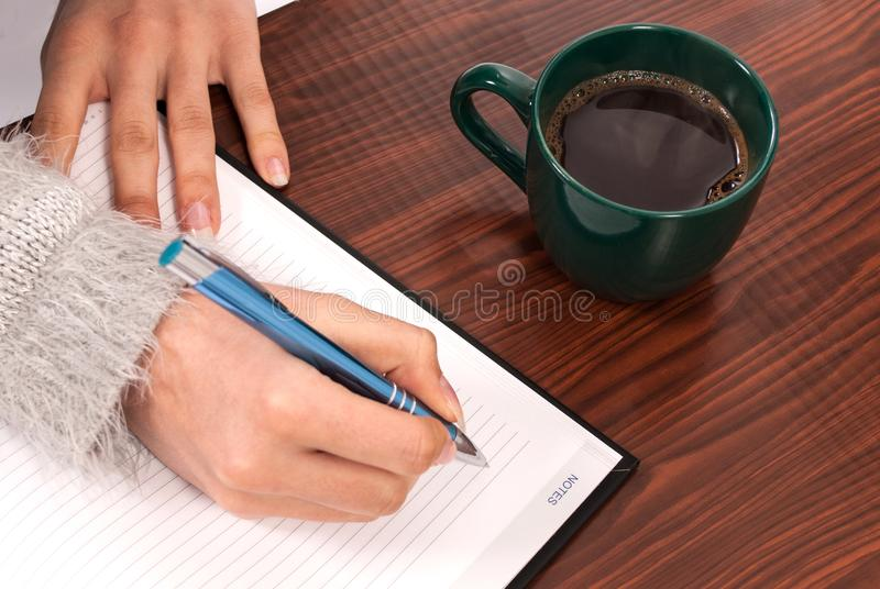 Kobiety pisze w notatnika na drewnianej biurka i napoju kawie obrazy royalty free