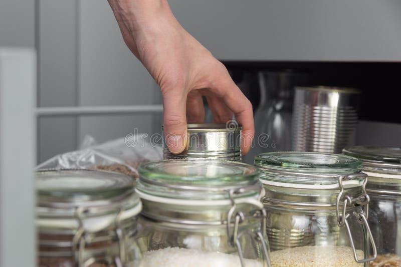 Kobiety podnosi rzecz od składowego hutch Mądrze kuchenny organizacji pojęcie obrazy stock
