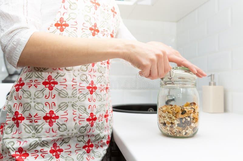 Kobiety podnosi rzecz od składowego hutch Mądrze kuchenny organizacji pojęcie zdjęcia stock