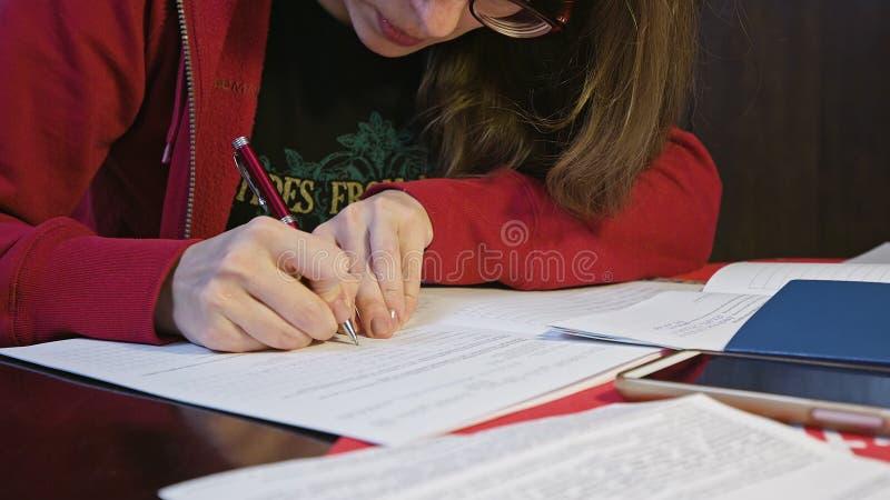 Kobiety podpisywanie w dokumencie lub Writing zdjęcia stock