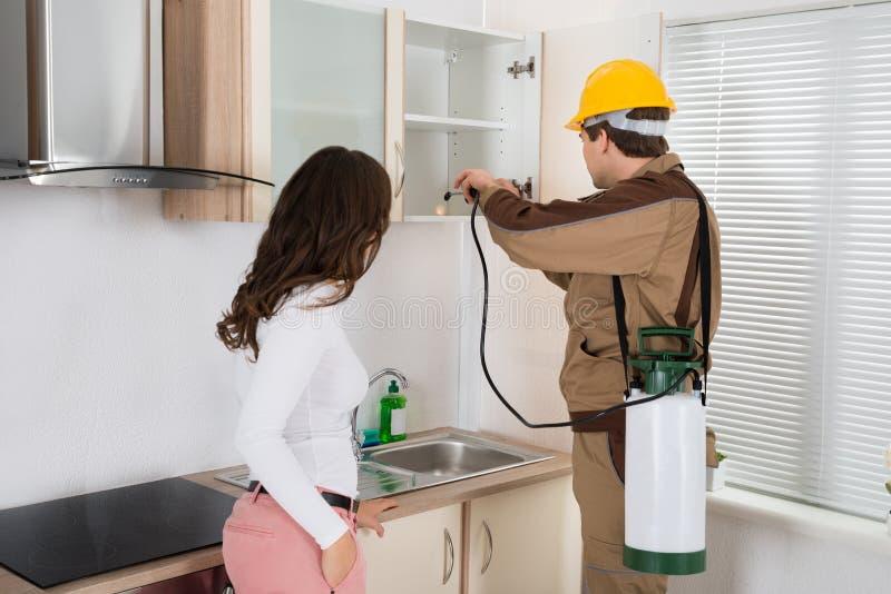 Kobiety pozycja Blisko pracownika opryskiwania pestycydu Na półce zdjęcie royalty free
