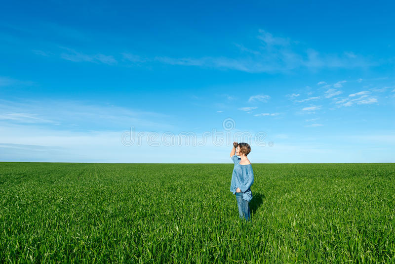 Kobiety pozycja i patrzeć daleki w zieleni polu obrazy royalty free