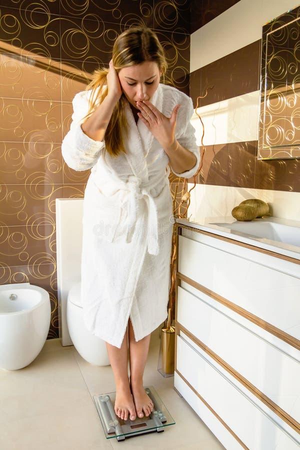 Kobiety pozycja na łazienki skala udaremniającej z zdjęcie stock