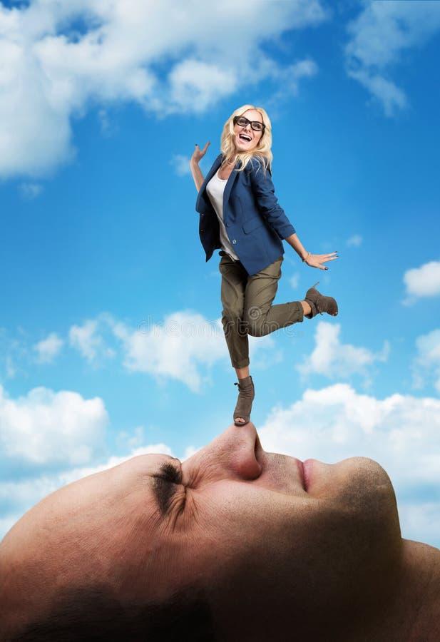 Kobiety pozycja na mężczyzna twarzy zdjęcia stock
