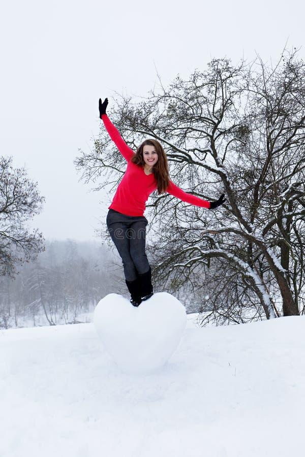 Kobiety pozycja na sercu śnieg zdjęcie royalty free
