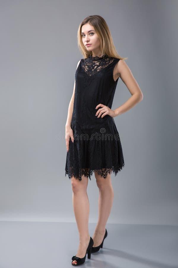 Kobiety pozycja w czarnej sukni nad szarym tłem obrazy royalty free
