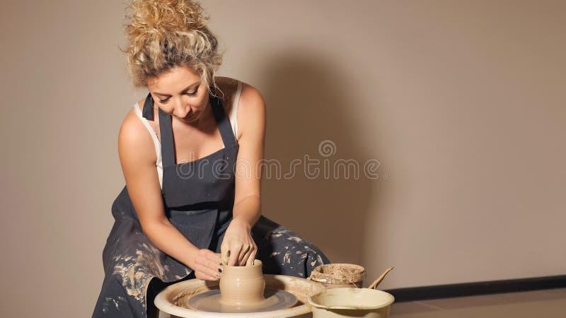 Kobiety pracuje na garncarki ` s toczą Ręki sculpts filiżankę od glinianego garnka obrazy stock