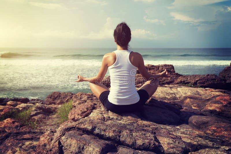 Kobiety praktyki joga przy nadmorski skałą zdjęcia royalty free