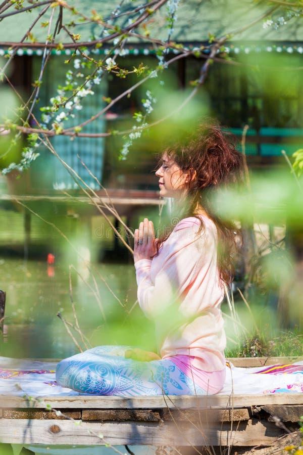Kobiety praktyki joga wiosny plenerowy letni dzień jeziorem siedzi w lotosowej pozycji z rękami w anjali mudra fotografia royalty free