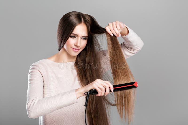 Kobiety prasowania włosy z włosy żelazem obrazy stock