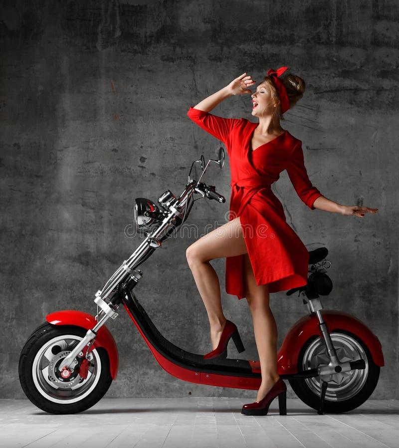Kobiety przejażdżka siedzi na motocykl hulajnogi rowerowego pinup czerwieni retro stylowej roześmianej uśmiechniętej sukni zdjęcie stock