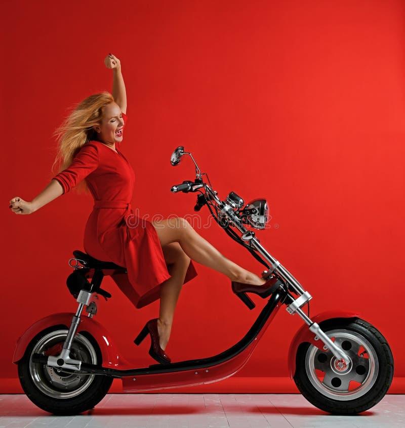 Kobiety przejażdżki elektrycznego samochodu nowego motocyklu rowerowa hulajnoga z ręka rozprzestrzeniającym wolność znakiem śmia  obraz stock