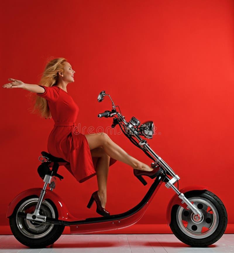 Kobiety przejażdżki elektrycznego samochodu nowego motocyklu rowerowa hulajnoga z ręka rozprzestrzeniającym wolność znakiem śmia  fotografia royalty free