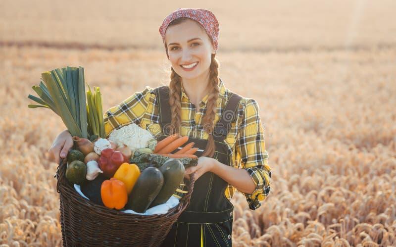 Kobiety przewożenia kosz z zdrowymi i w okolicy nadplanowymi warzywami zdjęcie royalty free