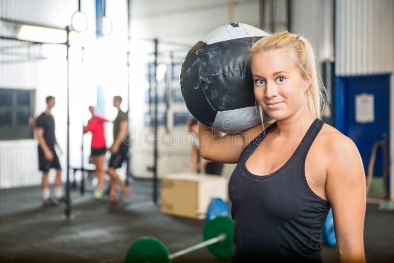 Kobiety przewożenia medycyny piłka Przy Crossfit Gym obrazy stock