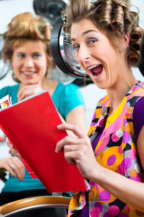 Kobiety przy fryzjerem z włosianą suszarką zdjęcie royalty free