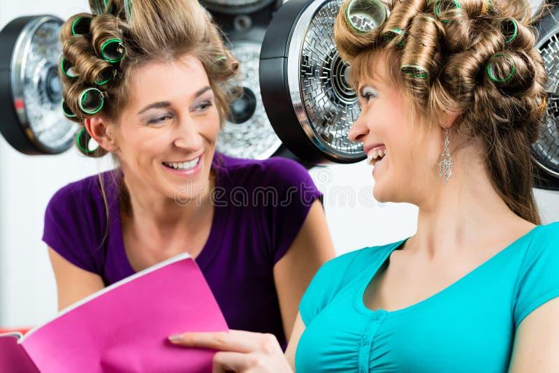 Kobiety przy fryzjerem z włosianą suszarką zdjęcia royalty free
