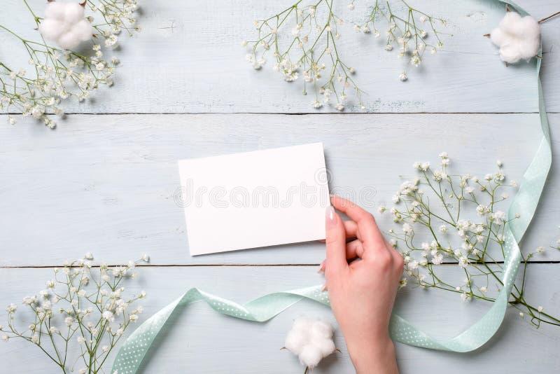 Kobiety ręka trzyma pustą papierową kartę na bławym drewnianym tle Wieśniaka stół z kwiatami, ślubna zaproszenie karta, list, obrazy stock