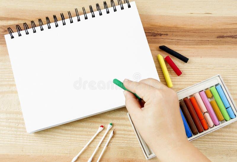 Kobiety ręki mienia oleju sztuki pastelowy zrywanie dla sztuka rysunku na papierze i setu pudełko kolorowe kredki na drewnie zgła obrazy stock