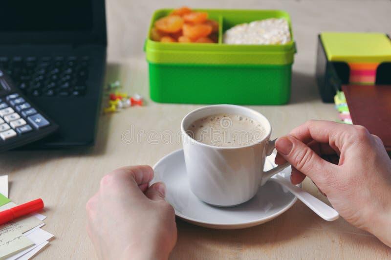Kobiety ręki trzymają filiżanka kawy podczas lunchu przy biurkiem w górę Nauka i i pracujący pojęcie zdjęcia royalty free