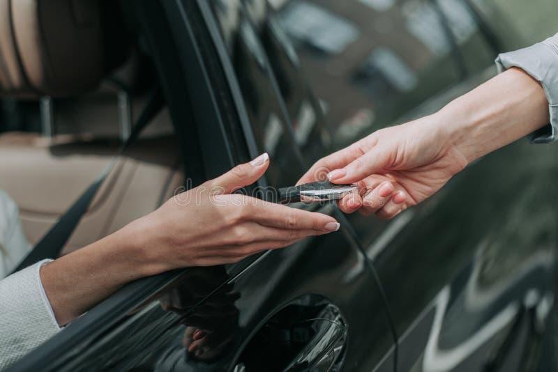 Kobiety ręka bierze klucz od samochodu sprzedawcy zdjęcie royalty free