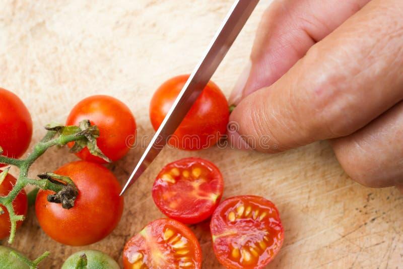 Kobiety ręka ciie czereśniowego pomidoru na drewnianej desce obrazy stock