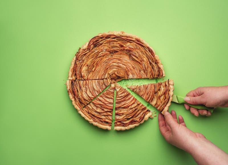 Kobiety ręka ciie jabłczanego kulebiaka Piec cukierki obraz stock