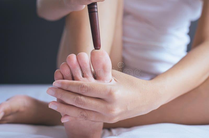 Kobiety ręka daje masażowi drewnianym kijem ona foots w sypialni, nożne podeszwy masaż, zakończenie up zdjęcia stock